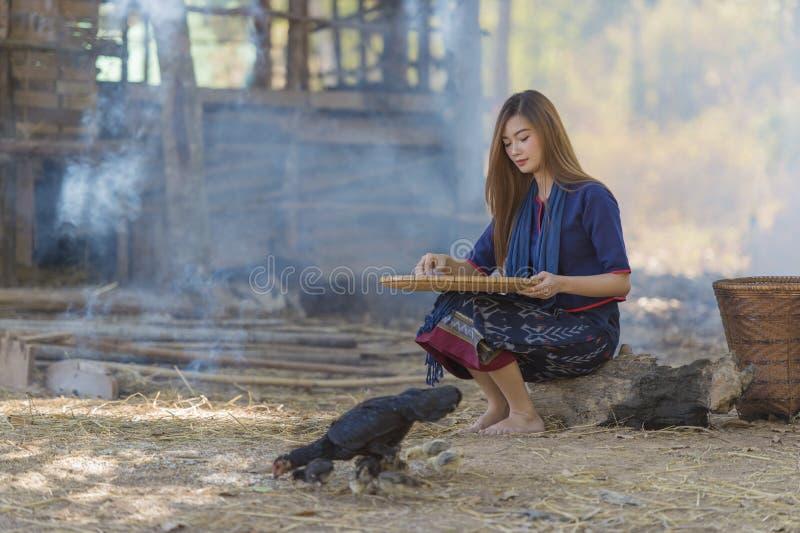 Asiatisches schönes Mädchen, das den Reis unterschiedlich zwischen Reis und Reishülsen trennt lizenzfreie stockbilder