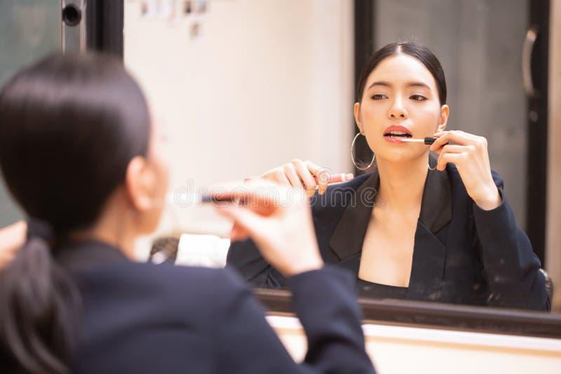 Asiatisches schönes und elegantes Mädchen, das den luxuriösen schwarzen Anzug sich setzt auf lipgloss Kosmetik auf Lippen trägt stockfoto