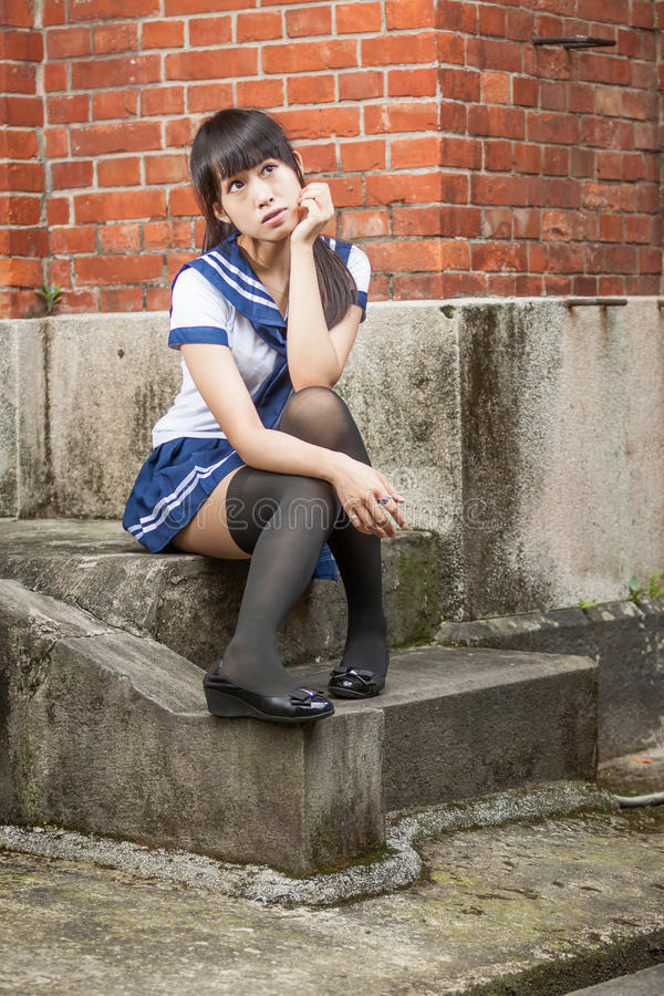 Asiatisches Schulmädchen, das vor Schule sitzt lizenzfreies stockbild
