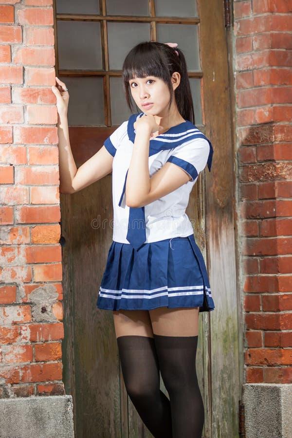 Asiatisches Schulmädchen in der Uniform außerhalb der Schule lizenzfreies stockbild