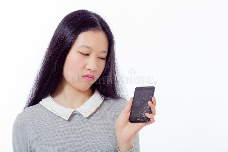 Asiatisches Schulmädchen mit gebrochenem Mobiltelefon lizenzfreie stockfotografie