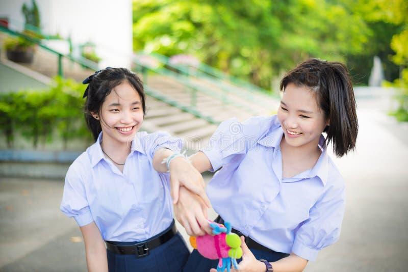 Asiatisches thailändisches hohes Schulmädchenstudenten-Paarspielen stockfoto
