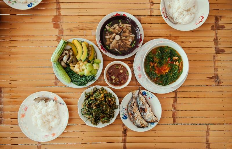 Asiatisches thailändisches lokales Lebensmittel diente auf weißer Platte auf Bambustischplatte lizenzfreies stockbild