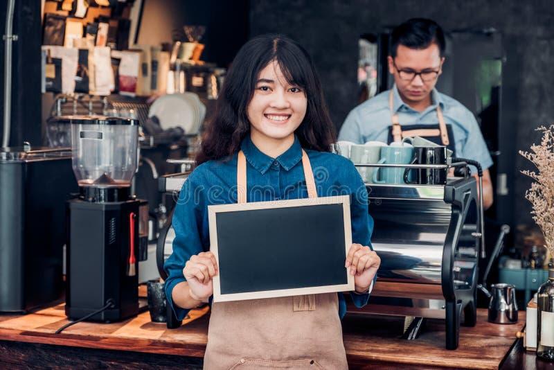 Asiatisches weibliches barista Abnutzungs-Baumwollstoffschutzblech, das leere Tafel Co hält lizenzfreie stockfotografie