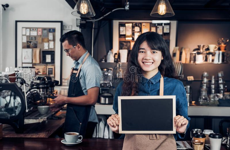 Asiatisches weibliches barista Abnutzungs-Baumwollstoffschutzblech, das leeres Tafelkaffeemenü an der Gegenbar mit Kollegen mit L stockfoto