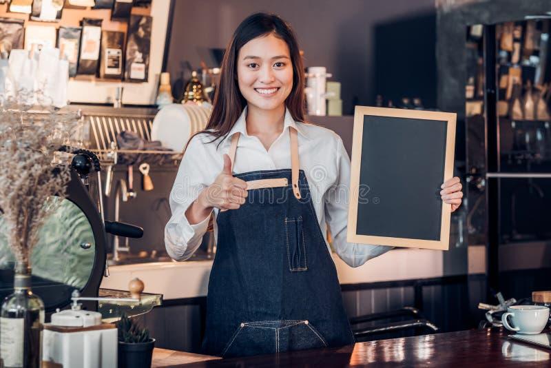 Asiatisches weibliches barista Abnutzungs-Baumwollstoffschutzblech greift oben am leeren blackboa ab lizenzfreies stockbild