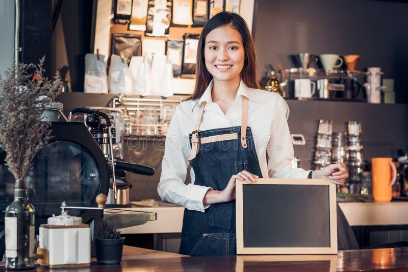 Asiatisches weibliches barista Abnutzungs-Baumwollstoffschutzblech und Halten leeres blackboar lizenzfreie stockfotos