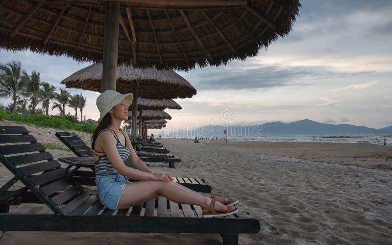 Asiatisches weibliches Sitzen auf Strand Recliner mit decken Regenschirm oben mit Stroh lizenzfreie stockfotos