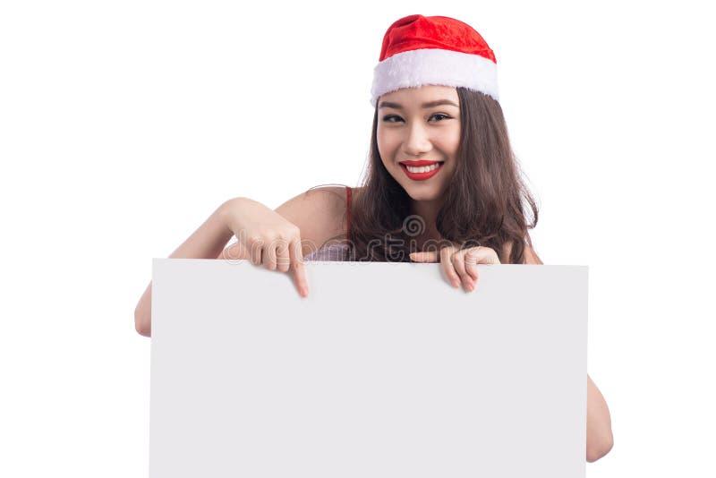 Asiatisches Weihnachtsmädchen mit Santa Claus kleidet das Halten des leeren Zeichens stockfoto