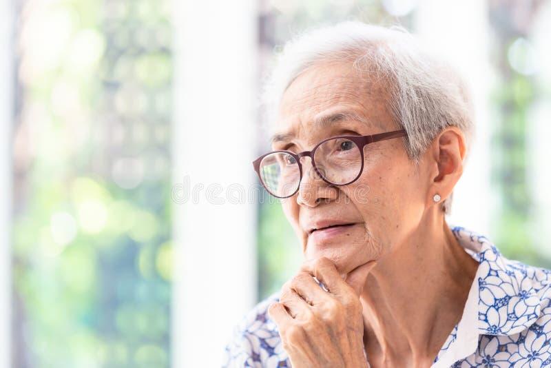 Asiatisk äldre kvinna i exponeringsglas som tänker med handen på hakan i hennes hem, hög kvinna som ler lycklig känsla arkivfoton