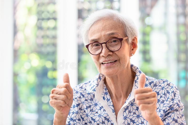 Asiatisk äldre kvinna i exponeringsglas som visar tummar som tillfredsställs upp med service som ler den höga kvinnashowtummen up arkivfoton