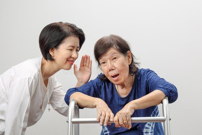Asiatisk äldre kvinnautfrågningförlust som är lomhörd royaltyfri foto
