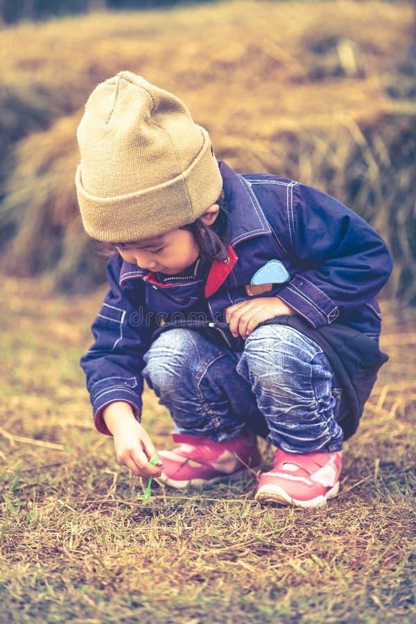 Asiatisk älskvärd flicka i hennes varma kläder för vinter som spelar på lantgården Nolla royaltyfri fotografi