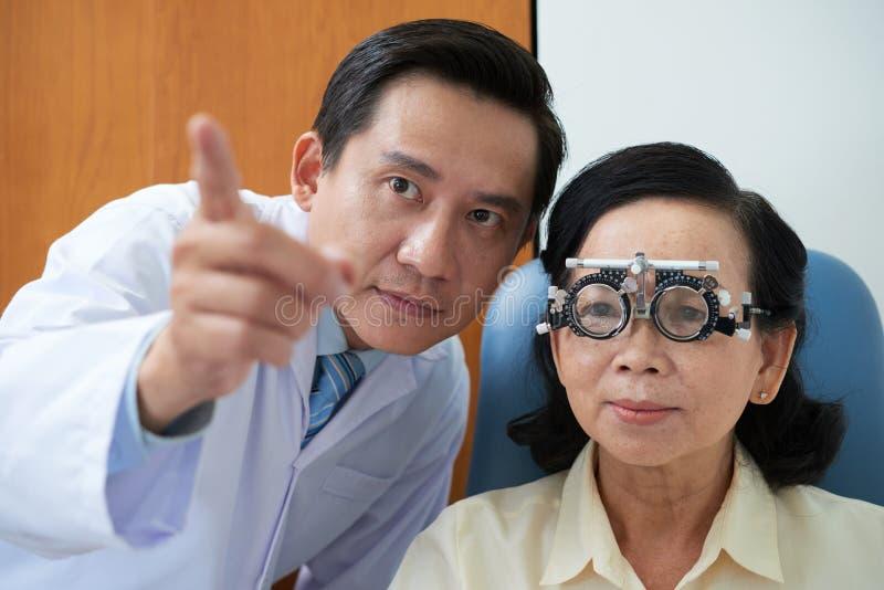 Asiatisk ögonläkare som arbetar med den mogna kvinnan royaltyfria foton