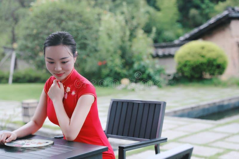 Asiatisk östlig orientalisk kinesisk kvinnaskönhet i röd cheongsam för traditionell forntida klänningdräkt i gammalt kulturmode f royaltyfri fotografi