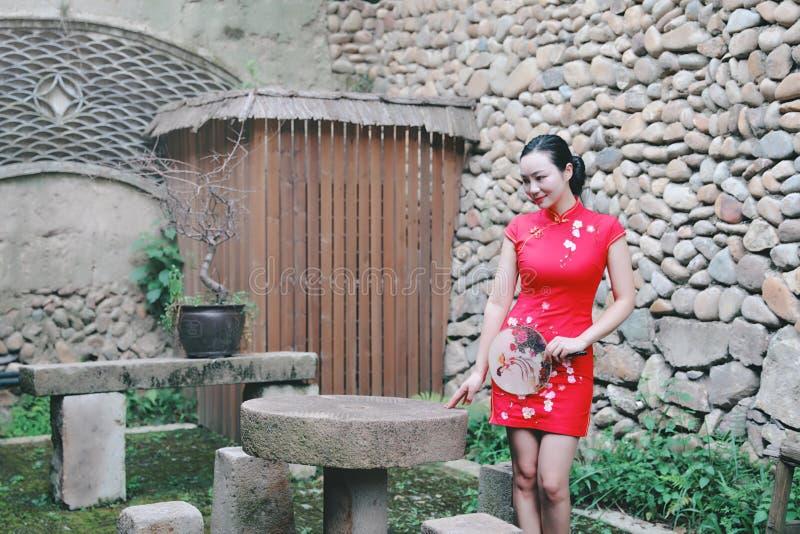 Asiatisk östlig orientalisk kinesisk kvinnaskönhet i röd cheongsam för traditionell forntida klänningdräkt med fanen i forntida g arkivfoto