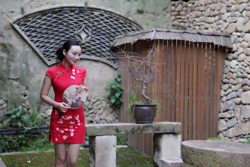 Asiatisk östlig orientalisk kinesisk kvinnaskönhet i röd cheongsam för traditionell forntida klänningdräkt med fanen i forntida g royaltyfria bilder