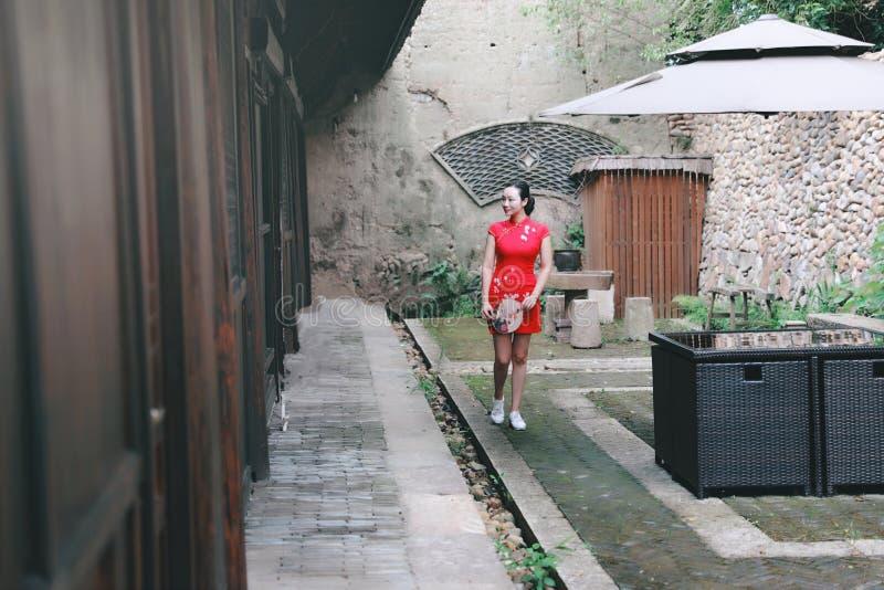 Asiatisk östlig orientalisk kinesisk kvinnaskönhet i röd cheongsam för traditionell forntida klänningdräkt med fanen i forntida g arkivfoton