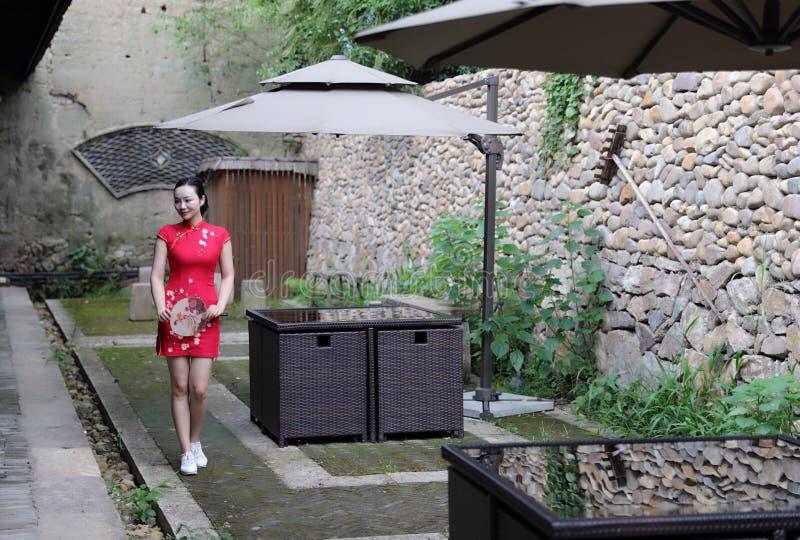 Asiatisk östlig orientalisk kinesisk kvinnaskönhet i röd cheongsam för traditionell forntida klänningdräkt med fanen i forntida g fotografering för bildbyråer