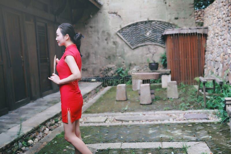 Asiatisk östlig orientalisk kinesisk kvinnaskönhet i röd cheongsam för traditionell forntida klänningdräkt med fanen i byggnad fö arkivbilder