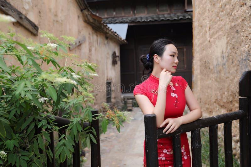 Asiatisk östlig orientalisk kinesisk kvinnaskönhet i röd cheongsam för traditionell forntida klänningdräkt i trädgårdstaket för f royaltyfria foton