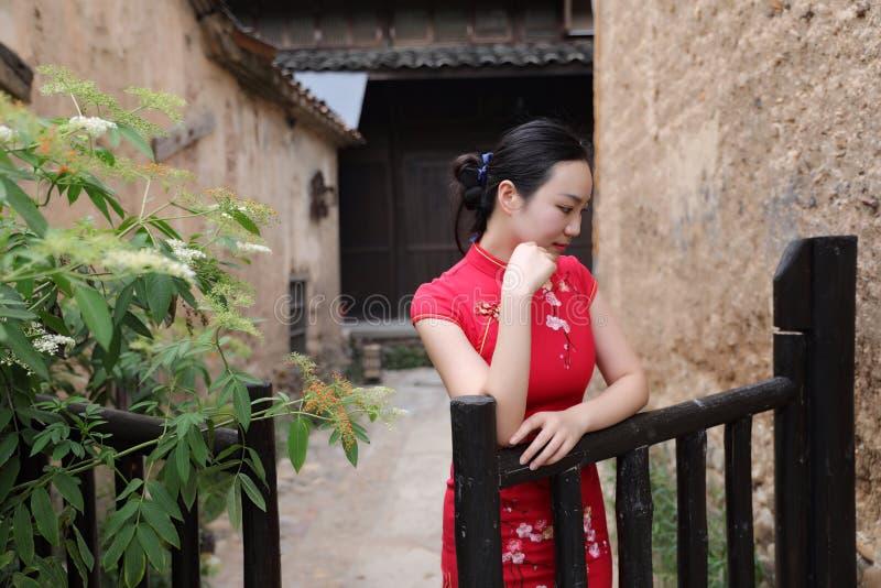 Asiatisk östlig orientalisk kinesisk kvinnaskönhet i röd cheongsam för traditionell forntida klänningdräkt i trädgårdstaket för f arkivbild