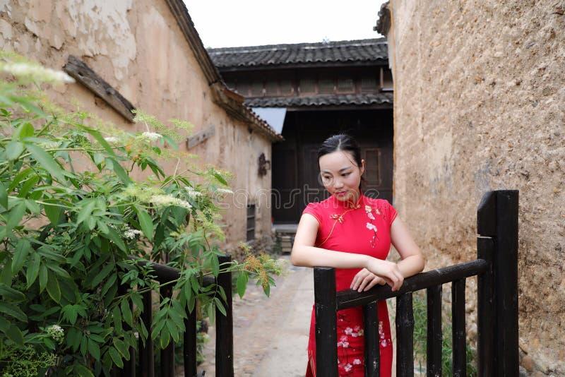 Asiatisk östlig orientalisk kinesisk kvinnaskönhet i röd cheongsam för traditionell forntida klänningdräkt i trädgårdstaket för f arkivfoton