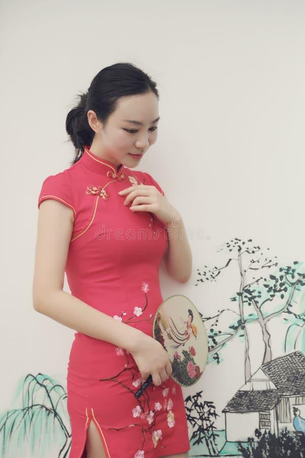 Asiatisk östlig orientalisk kinesisk kvinnaskönhet i röd cheongsam för traditionell forntida klänningdräkt i forntida vit vägg me fotografering för bildbyråer