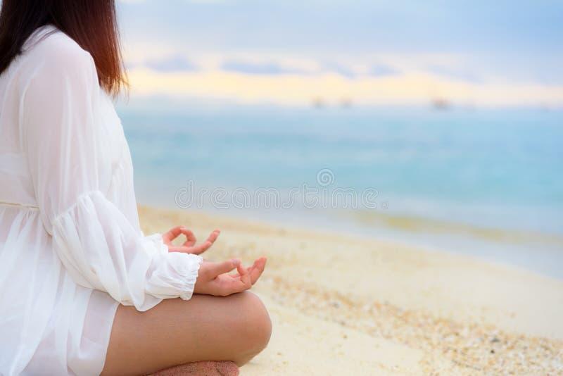 Asiatisk övande yoga för ung kvinna på stranden royaltyfria bilder