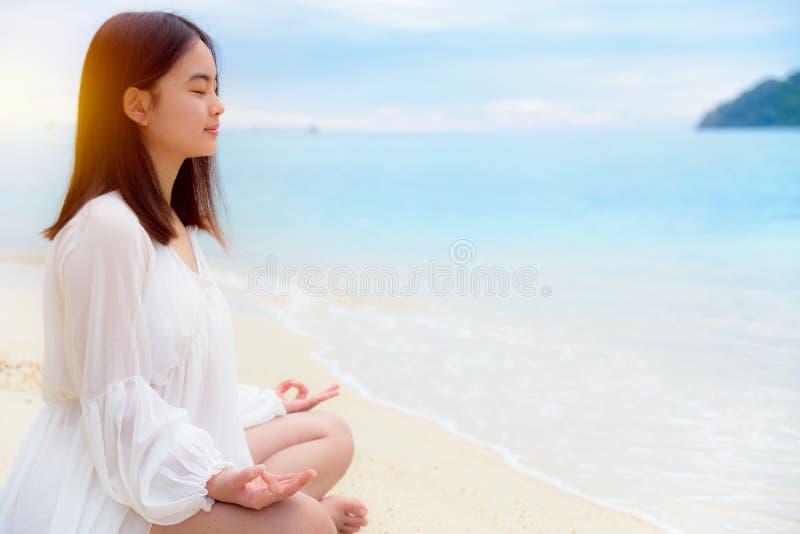 Asiatisk övningsyoga för ung kvinna på stranden royaltyfri bild