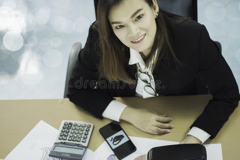 Asiatisk affärskvinna för bästa sikt som lyckligt ler, med dokumentet försäljningarna av VR-hörlurar med mikrofon i världsmarknad royaltyfri bild