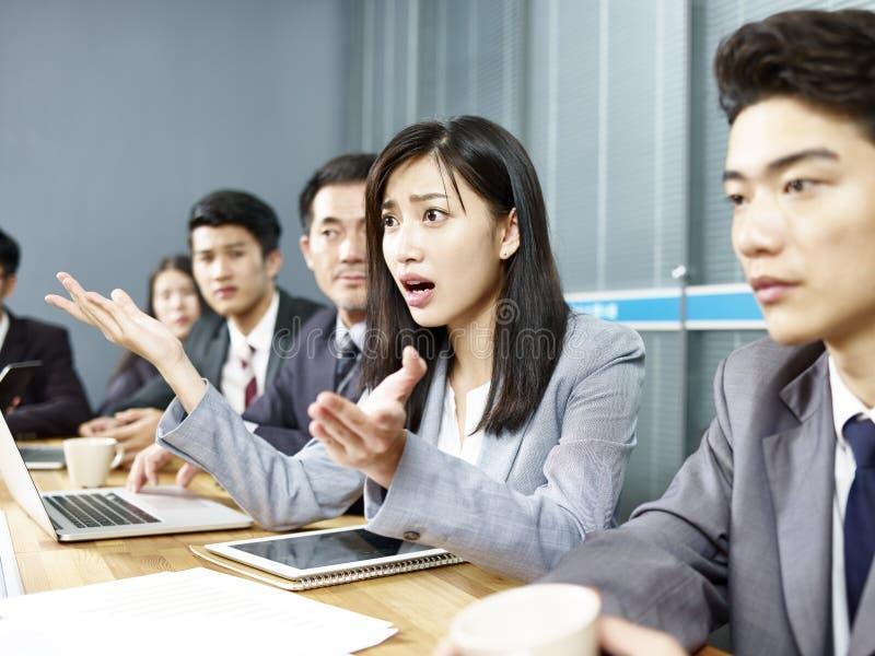 Asiatisk affärskvinna i en upphettad diskussion fotografering för bildbyråer