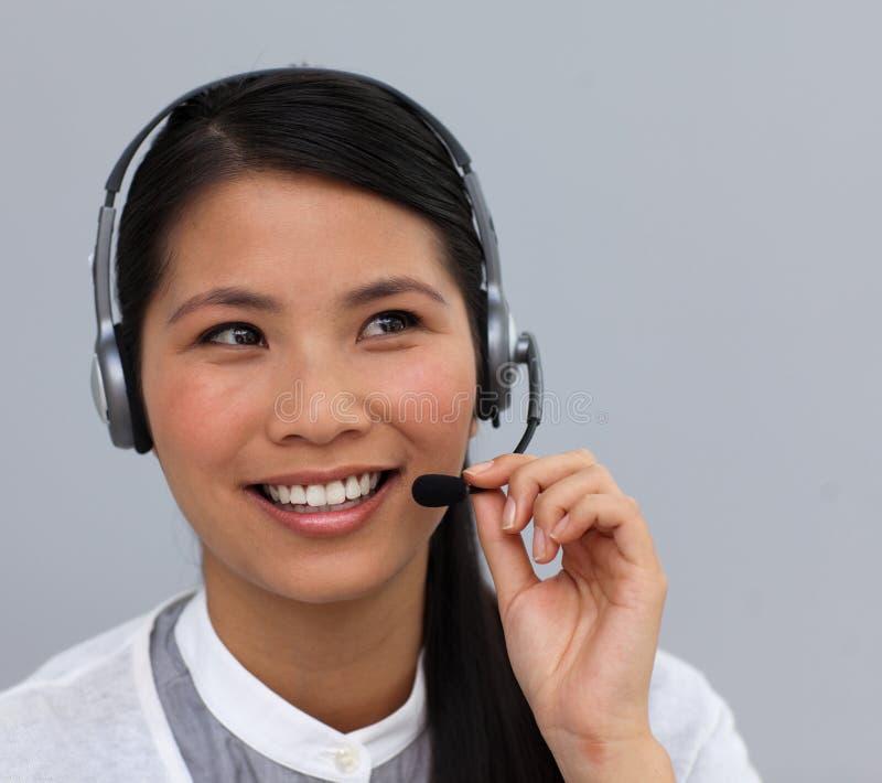 Asiatisk affärskvinna med hörlurar med mikrofon på royaltyfri fotografi