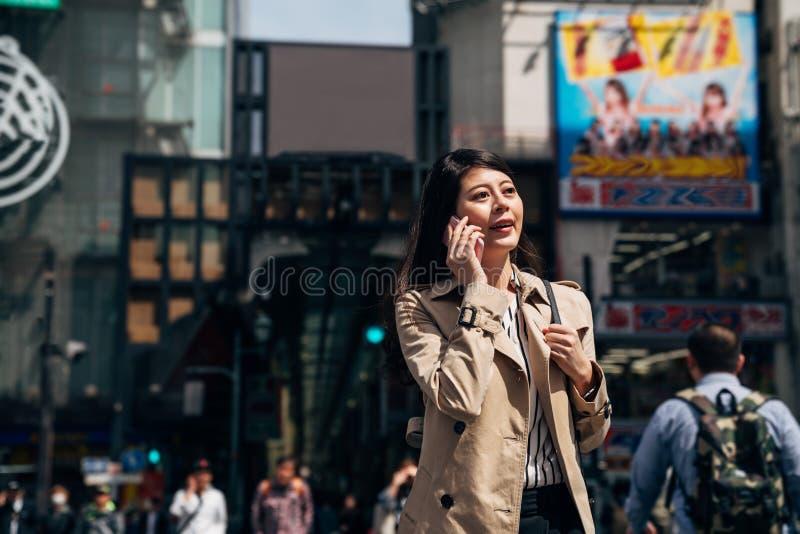 Asiatisk affärskvinna på att gå för mobiltelefon arkivfoton