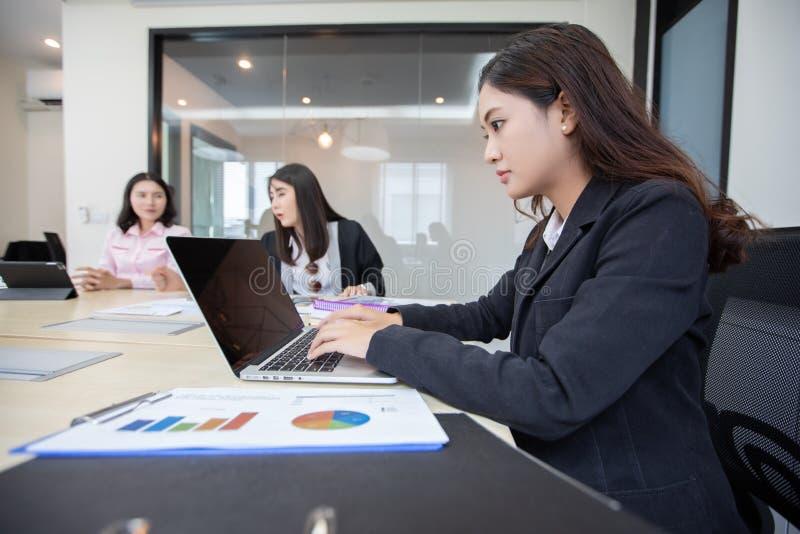 Asiatisk affärskvinna som är allvarlig om arbetet och använder anteckningsboken för affärspartners som diskuterar dokument och id fotografering för bildbyråer