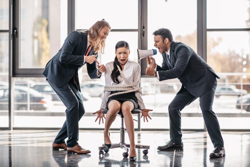 Asiatisk affärskvinna som är destinerad med repet på stol medan affärsmän som skriker på henne med megafonen arkivfoton