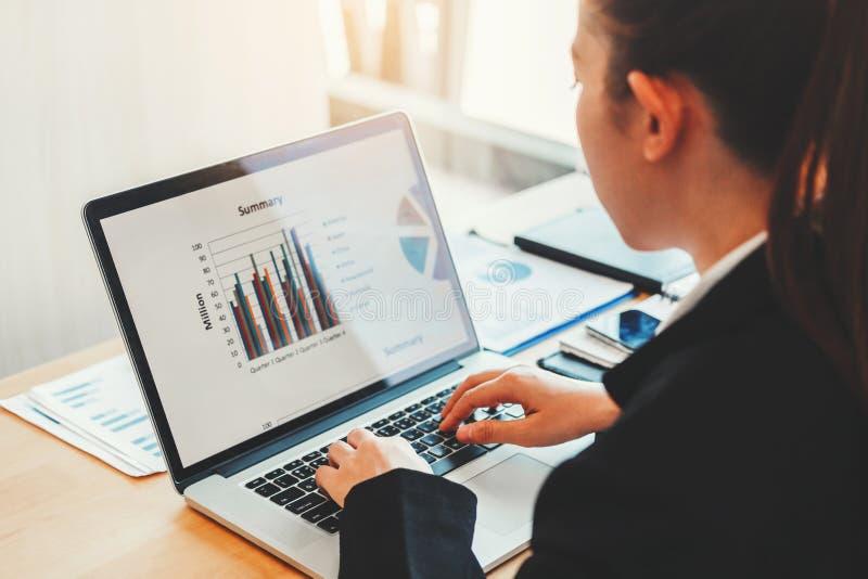 Asiatisk affärskvinna som använder bärbar datordatoren som arbetar det nya projektet som diskuterar finansiella grafdata för nytt arkivbilder