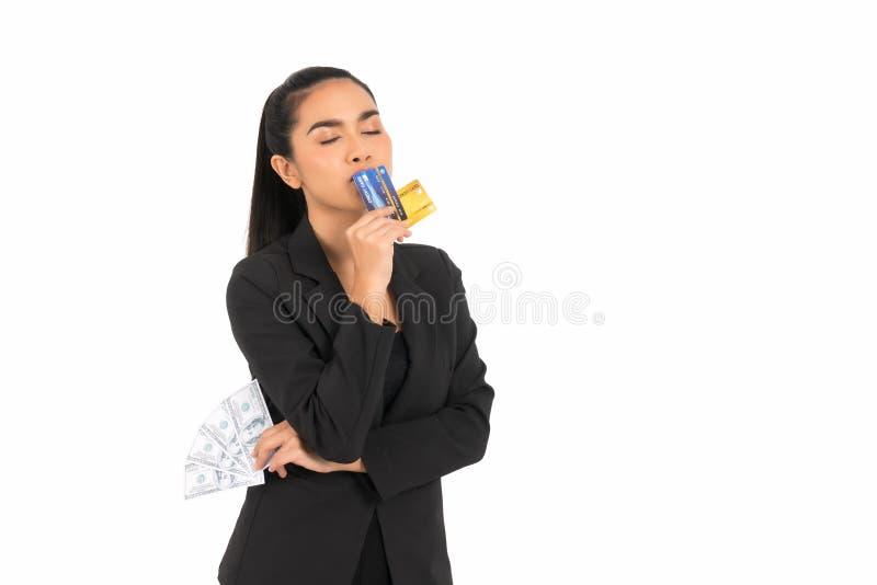 Asiatisk affärskvinna som bär en svart dräkt som rymmer kreditkortar och pengar royaltyfria foton