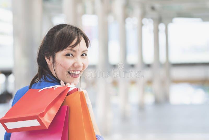 Asiatisk affärskvinna som förestående rymmer färgrika pappers- shoppingpåsar arkivbilder