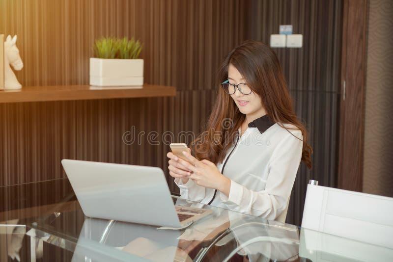 Asiatisk affärskvinna som framme använder en telefon av en bärbar dator fotografering för bildbyråer