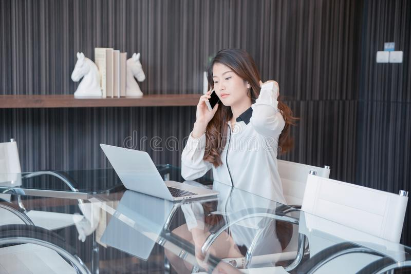 Asiatisk affärskvinna som framme använder en telefon av en bärbar dator arkivbild