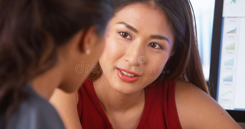 Asiatisk affärskvinna som har en diskussion med den mexicanska kollegan royaltyfri foto