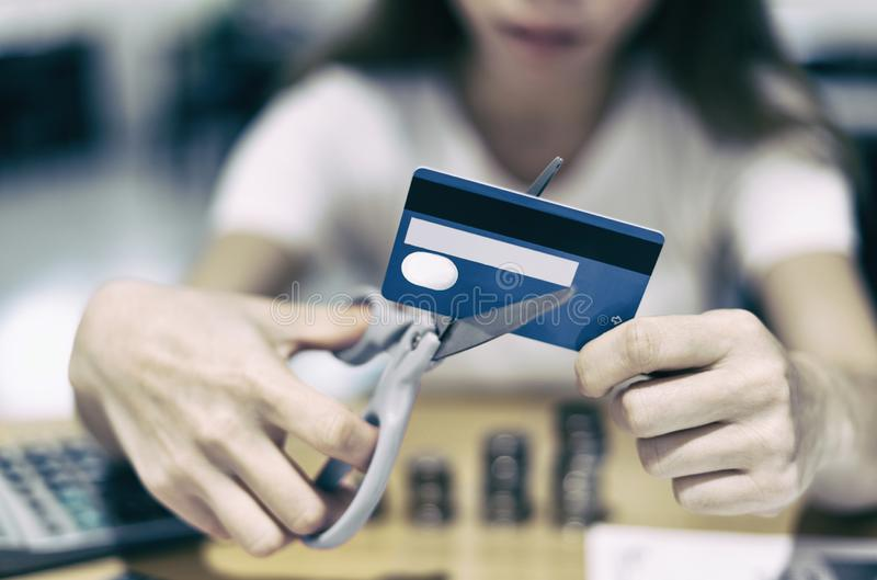 Asiatisk affärskvinna som klipper kreditkorten med sax i tappningfilterbakgrund arkivfoton