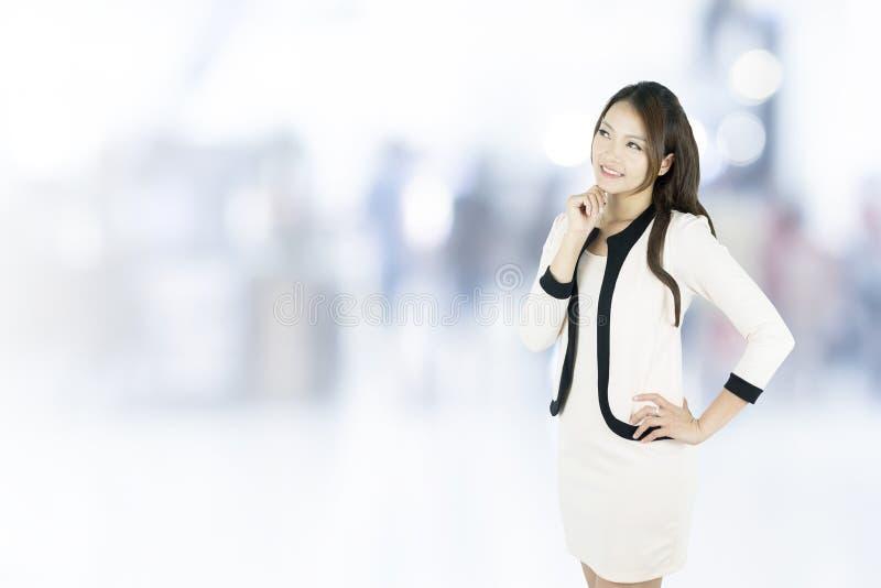 Asiatisk affärskvinna som tänker le att se upp på kontorsbakgrund royaltyfria foton