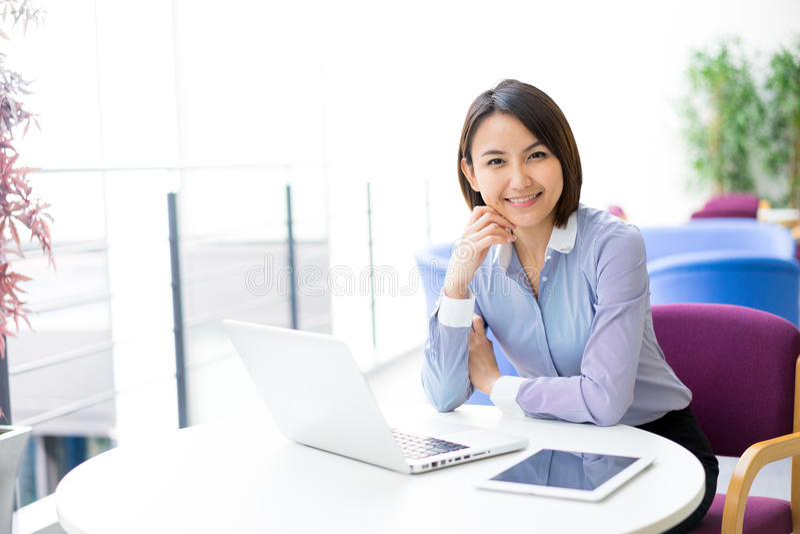 Asiatisk affärskvinna som talar genom att använda hennes hörlurar med mikrofon i kontoret royaltyfri fotografi