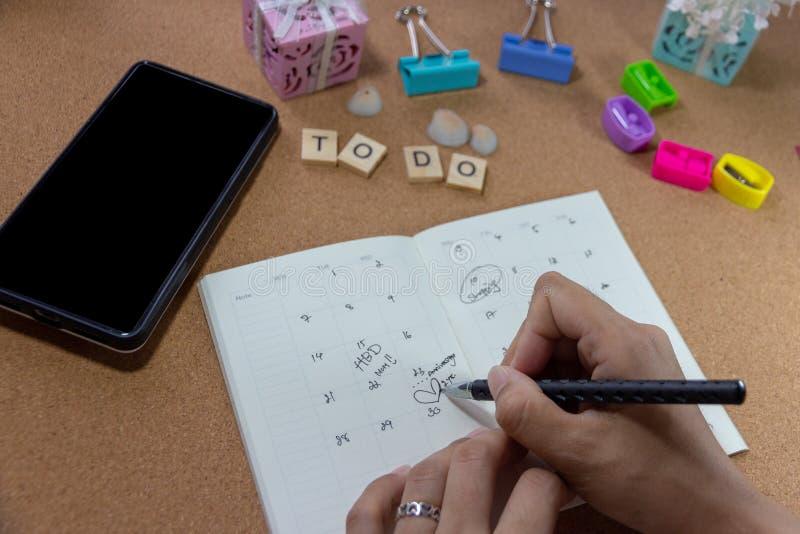 Asiatisk affärskvinna som ut fyller a för att göra listan och kontrollerar tidsbeställningar arkivfoton