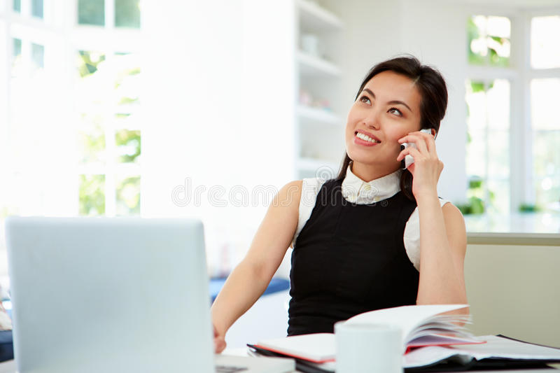 Asiatisk affärskvinna Working From Home som använder mobiltelefonen royaltyfri foto