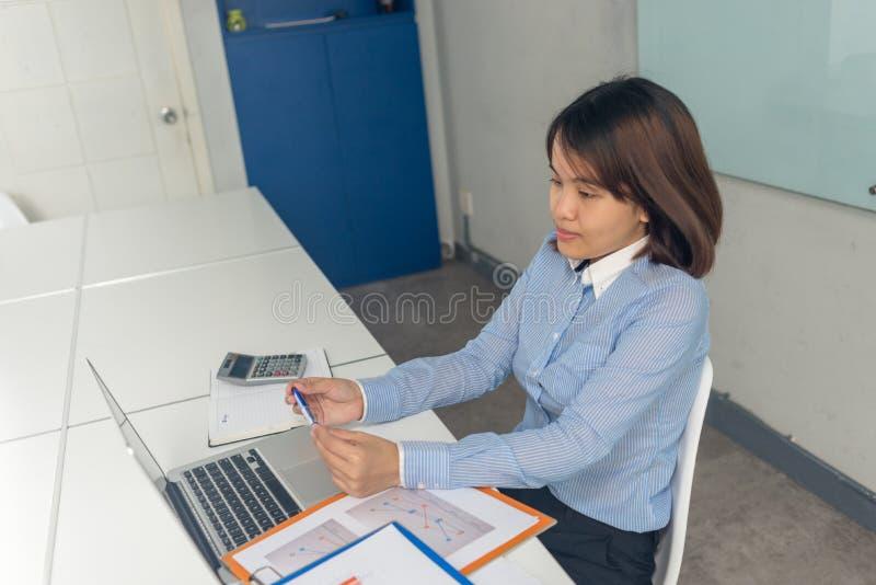 Asiatisk affärskvinnainnehavpenna som tänker om affären royaltyfria foton