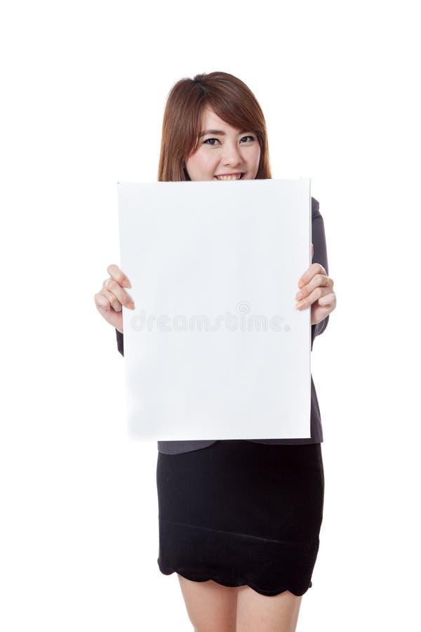 Asiatisk affärskvinnashow ett vertikalt tomt tecken och leende arkivfoto
