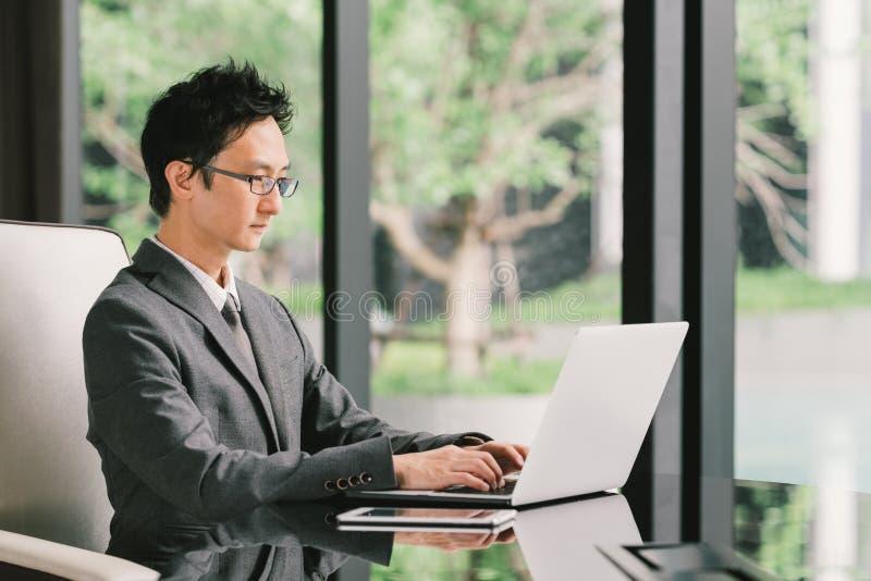 Asiatisk affärsman eller entreprenör på arbete, genom att använda bärbar datordatoren och den digitala minnestavlan i utövande ko fotografering för bildbyråer